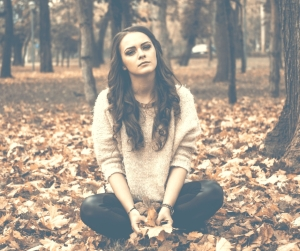 complete: God has the answer to our brokenness and pain - girl sitting with dried autumn leaves